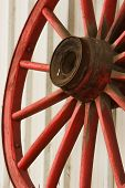 image of ox wagon  - Close up of a red antique wagon wheel leaning against a steel shed - JPG
