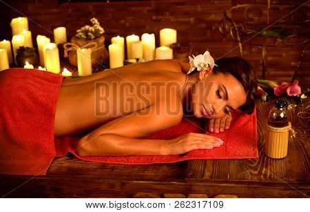 poster of Ayurveda massage of woman in spa salon. Girl on candles background in massage spa salon. Thai massag