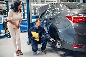 Auto Car Repair Service Center. A Female Customer And Mechanic Checking Car Breaks poster