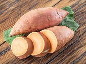 Sweet potatoes on the old wooden table. poster