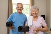 Active healthy senior couple holding yoga mats while going together to training. Happy fitness elder poster