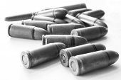 Many Bullets On A Surface Isolated White Background. Brass Riffle Cartridge Gun Ammunition. Black An poster