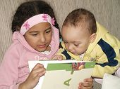 foto of storytime  - sisters sitting and reading a book together - JPG