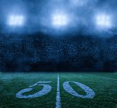 American Football Stadium at night 50 yard line. Stadium lights on a misty clouded night. Nobody in  poster