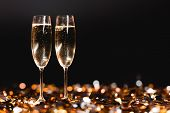 Champagne Glasses On Golden Confetti On Black For New Year Celebration poster