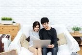 Young Asian Couple Looking At Laptop Computer To Search For Travel Plan, Book Hotel Room, Buy Ticket poster