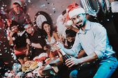Bearded Man In Rad Cap Opening Bottle Of Champagne. Santa Claus Costume. People In Red Caps. Happy N poster