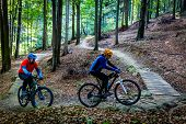 Mountain biking women and man riding on bikes in early spring mountains forest landscape. Couple cyc poster
