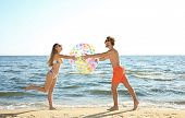 Happy Young Couple In Beachwear Playing With Inflatable Ball On Seashore poster