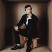 Young Businessman In Black Suit In Cardboard Box. Young Man In Suit. Life In Little Cardboard Box. U poster