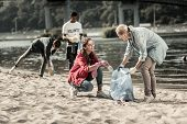 Loving Responsible Mother Volunteering On The Beach With Her Three Children poster