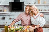 Affectionate Adult Couple Hugging And Looking At Camera During Salad Preparation For Dinner In Kitch poster