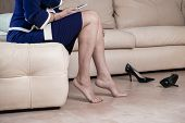 Business Woman Touching Feet With Her Hand. Cropped Image Of Woman In Black High Heels Massaging Her poster
