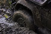 Fragfment Of Car Stuck In Dirt, Close Up. Dirty Offroad Tire Covered With Mud. Wheel With Cloud Of S poster