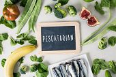 a signboard with the text pescatarian, for vegetarian people who eat fish, and a pile of some differ poster