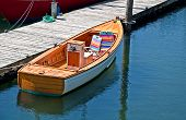 stock photo of dingy  - This small dingy boat is tied up at a dock with folding lawn chairs in the bow - JPG