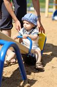 stock photo of seesaw  - Child is swinging on the seesaw at a playground - JPG