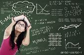 stock photo of formulas  - Confused college student with formulas on the blackboard and covering her head by textbook - JPG