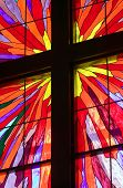stock photo of christian cross  - A portion of a stained glass window with wooden molding forming a Christian cross - JPG