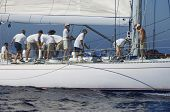 picture of work crew  - Side view of several crew members working on the sailboat at sea - JPG