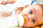 stock photo of suck  - Lovely blue eyed baby feeding on milk bottle