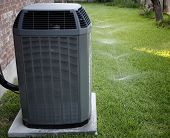 stock photo of condensation  - Air conditioner and working sprinklers close - JPG