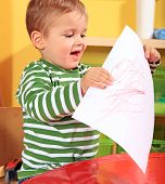 Cute caucasian toddler shows his drawn picture in kindergarten.
