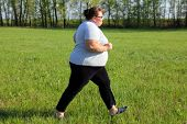 sport - overweight woman running on green meadow