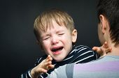 stock photo of sob  - Portrait of a crying child on hands a father - JPG