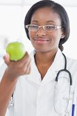Portrait of a smiling female doctor holding an apple at a bright hospital