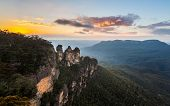 pic of three sisters  - Rising sun illuminates the Three Sisters rock formation in the valley from Echo Point overlooking the majestic Blue Mountains near Sydney NSW Australia - JPG