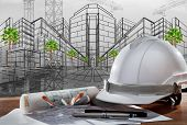 stock photo of engineering construction  - safety helmet and architect pland on wood table with sunset scene and building construction - JPG