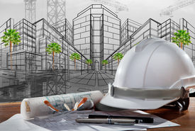 image of land development  - safety helmet and architect pland on wood table with sunset scene and building construction - JPG