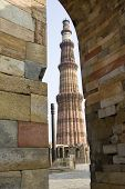 foto of qutub minar  - Qutub Minar and Iron Pillar viewed though stone wall corner and arch Delhi India Asia - JPG
