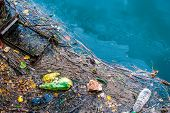 stock photo of sewage  - Water pollution old garbage and oil patches on river surface - JPG