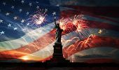 stock photo of flashing  - Statue of Liberty on the background of flag usa sunrise and fireworks - JPG