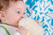 picture of teats  - Six month old baby drinking milk from a bottle with the teat - JPG