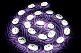 foto of rune  - Runes illuminated in a spiral pattern purple background - JPG