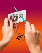 picture of magnetic tape  - Woman rewind a retro cassette with loose tape using a pencil - JPG