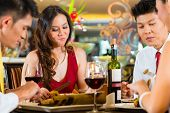 foto of chinese menu  - Two Asian Chinese Couples or friends or business people toasting during dinner or lunch in a elegant restaurant with red wine glasses - JPG
