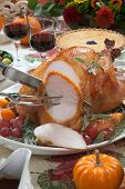 foto of kumquat  - Carving roasted turkey on a server tray garnished with fresh figs grape kumquat and herbs on fall harvest table - JPG