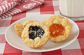 stock photo of shortbread  - Gourmet shortbread cookies with peach and blackberry jam filling with milk - JPG
