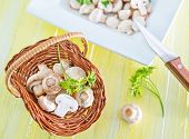 foto of agaricus  - raw mushrooms in basket and on a table - JPG