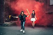 stock photo of teen smoking  - Two Bad girls with Molotov cocktail and red smoke bomb in the street - JPG