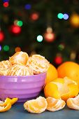 picture of tangerine-tree  - Sweet tangerines and oranges on table on Christmas tree background - JPG