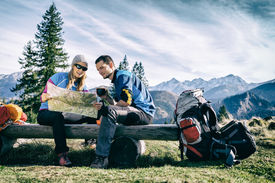 stock photo of family planning  - Man and woman hikers hiking in mountains - JPG
