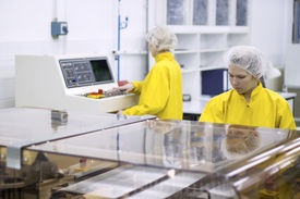 picture of pharmaceuticals  - Two pharmaceutical workers wearing protective work wear. Female workers at pharmaceutical factory. - JPG