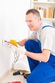 stock photo of  multimeter  - Electrician checking socket voltage with digital multimeter - JPG