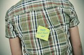 image of fool  - a young caucasian man wearing a plaid patterned shirt with a yellow sticky note attached to his back with the text happy april fools day written in it - JPG