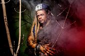 stock photo of werewolf  - Werewolf with long nails and hair dreadlocks among the branches of the tree - JPG